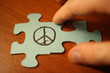 Quadro hand connects puzzles of sign of peace. World Day of Peace.