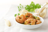 shrimps with garlic, olive oil and parsley in sherry sauce in a white bowl, spanish tapas appetizer gambas al ajillo, white napkin and herb garnish in the background, copy space - 182885195