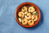 shrimps or prawns and garlic in olive oil with parsley in a brown tapas bowl, spanish appetizer on a blue tablecloth background, flat top view from above, copy space - 182885382
