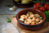 shrimps or prawns in garlic and olive oil in a tapas bowl, a spanish appetizer on a wooden board, potatoes, tomatoes and herbs in the background, dark rustic style - 182885565