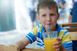 Cute smiling boy drinking juice with the straw in a street cafe.