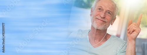 Fotobehang Muziek Portrait of cheerful mature man listening music with earphones, light effect