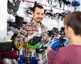 Master fixing roller-skates for boy customer in sports store - 182890972