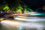 sea waves are illuminated by the light of lamps located on the quay of the resort
