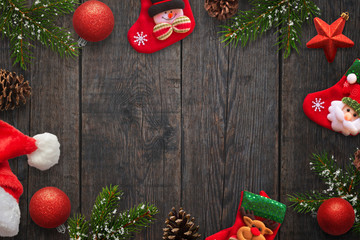 Christmas decorations on dark wooden table. Free space in the middle for text. Top view.