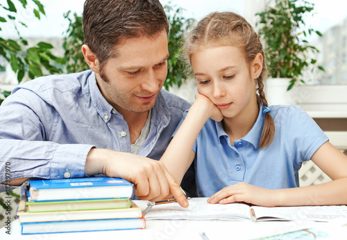 Father helping daughter with homework at home. - 182897970