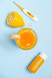 Ginger shot healthy drink with curd in a plastic bottle and thermometer on blue background. Immunity Boosting Tonic. Space for text - 182901381