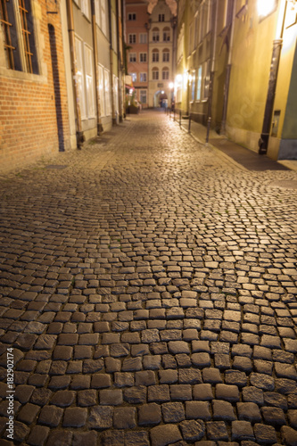 View of cobblestone paving on the empty Kramarska Street at the Main Town (Old Town) in Gdansk, Poland, in the evening Poster