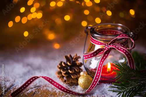 Advent, Christmas  -  Burning candle in snow landscape with bokeh background