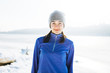 Smiling young woman wearing sport clothing is standing outdoor in winter
