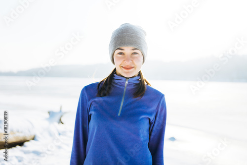 Fototapeta Smiling young woman wearing sport clothing is standing outdoor in winter