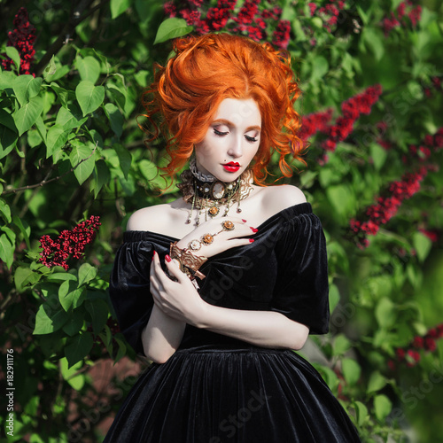 A woman is a vampire with pale skin and red hair in a black dress and a necklace on her neck against the background of nature Poster
