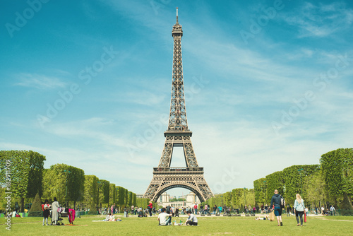 Deurstickers Eiffeltoren Paris, France - May 6,2016 : Tourists chilling in park near Eiffel Tower Paris, France. In year 2016 more than 15 million tourists visited the city of Paris.