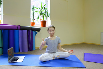 Little girl sits on floor in lotus position.