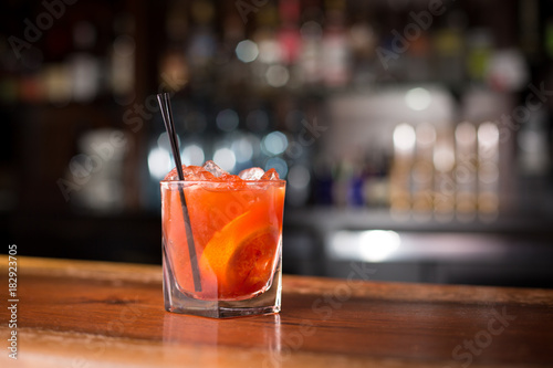 Close up on blood orange cocktail with bar background