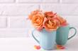 Fresh orange roses in blue cups