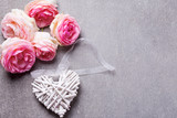 Fresh  pink roses and decorative white heart on grey slate background. - 182924136