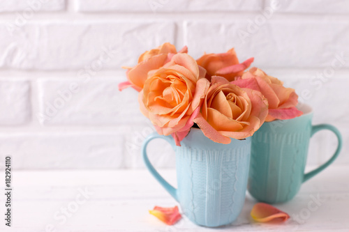 Poster Fresh orange roses in blue cups