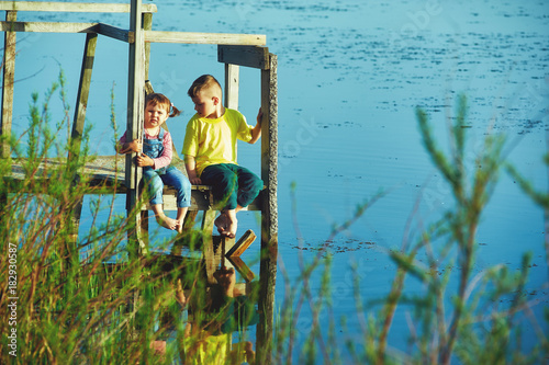 Sticker Children sit on a wooden bridge at the reservoir .Brother and sister on vacation in the countryside at sunset