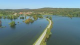 AERIAL: Lone road leads to small village through submerged countryside on sunny fall day. Small town evades horrific natural disaster as overflowing rivers and heavy rainfall flooded - 182937927