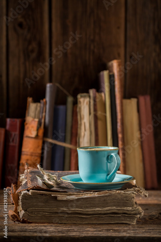 Wall mural Coffee in blue porcelain on book in library