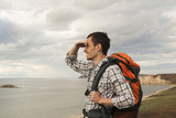 young tourist man with a backpack on the lake, Lake Baikal, summer tourist walk, freedom and happiness - 182942740