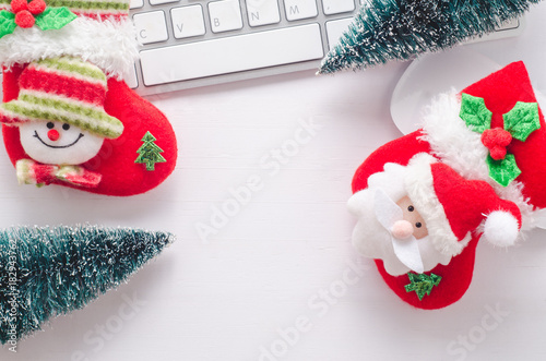 Wooden working table with computer keyboard, mouse , christmas socks and tree. View from above with copy space.