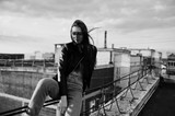Portrait of a gorgeous young woman in black leather jacket, jeans and sneakers sitting on handrails on the roof with picturesque view of a park. Black and white photo. - 182944533