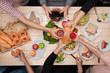 Enjoying dinner with friends.  Top view of group of people having dinner together while sitting at wooden table - 182944956
