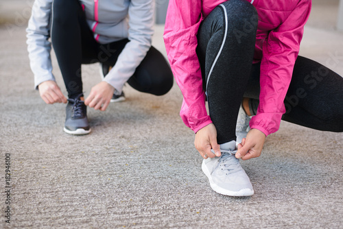 Fototapeta Close up of women lacing sport shoes and getting ready for urban running. Fitness workout and healthy lifestyle concept.
