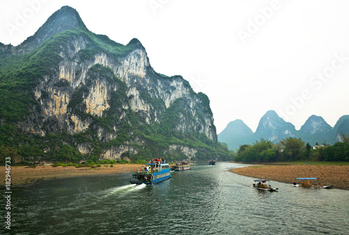 Foto op Canvas Guilin China. Li River (Lijiang River). Numerous tourists take pictures of the natural landmark of Fresco Hill from the pleasure boats sailing from Guilin to Yangshuo on a foggy day