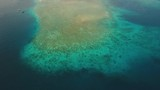Aerial view coral reef, atoll with turquoise water in the sea.Tropical atoll, coral reef in ocean waters. 4K video. Travel concept. Aerial footage. - 182950522