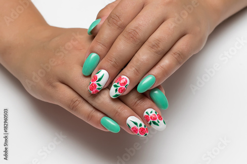 Foto op Plexiglas Manicure minty white oval manicure with painted red flowers on a white background