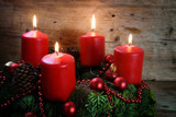 Advent wreath from fresh fir tree branches with four red burning candles and christmas decoration on rustic  wood - 182966132
