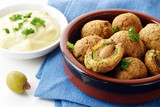 Green olives baked in parmesan dough with a creamy garlic dip, finger food for the party buffet, spanish tapas appetizer, brown ceramic bowl on a blue naplin on a white table - 182966380