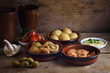 Rustic party appetizers such as baked olives, prawn shrimps, potatoes, tomato and garlic dip, spanish tapas served on a wooden board, dark background with copy space - 182966512