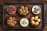 Spanish tapas such as baked olives, prawn shrimps, potatoes, tomato and garlic dip, party  appetizers on a rustic wooden tray, flat top view from above - 182966592