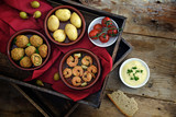spanish tapas as party appetizers, baked olives, prawn shrimps, potatoes, tomato and garlic dip on a wooden tray with a red napkin on rustic wood, warm dark country style, flat top view from above - 182966721