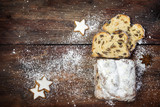 christmas background, traditional german criststollen cake sprinkled with icing sugar, cinnamon cookies and anise stars on a dark rustic wooden board, top view from above, copy space - 182966979