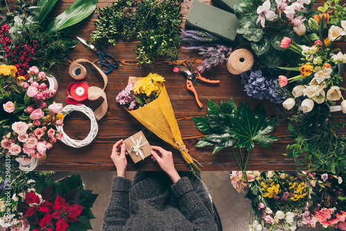 cropped image of florist holding postcard to add to bouquet