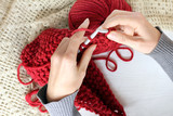 preparation of warming items of wardrobe/ hand work on knitting needles, scarf of red thread - 182969527