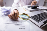 Auditor Checking Invoice Using Magnifying Glass