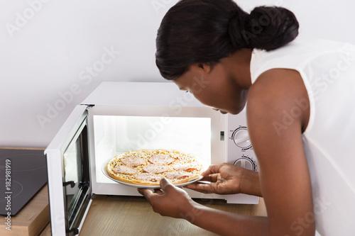 Papiers peints Pizzeria Woman Baking Pizza In Microwave Oven