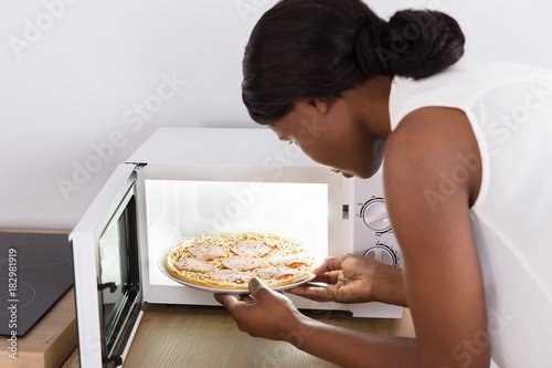 Woman Baking Pizza In Microwave Oven Poster