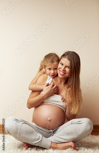 Sticker   Happy family relaxing at home. Attractive pregnant mum hugging her cute daughter.