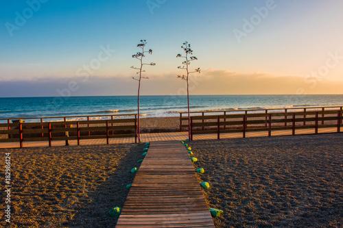 Plexiglas Pier Beach. Summer sunset beach. Costa del Sol, Andalusia, Spain.