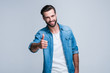 Great work! Handsome young man looking at camera with smile and gesturing thumb up while standing against white background