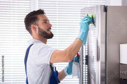 Papiers peints Echelle de hauteur Male Janitor Cleaning Refrigerator