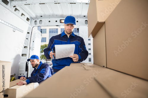 Mover Looking At His Partner Writing On Clipboard - 182997397