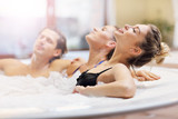 Group of friends enjoying jacuzzi in hotel spa - 182999315
